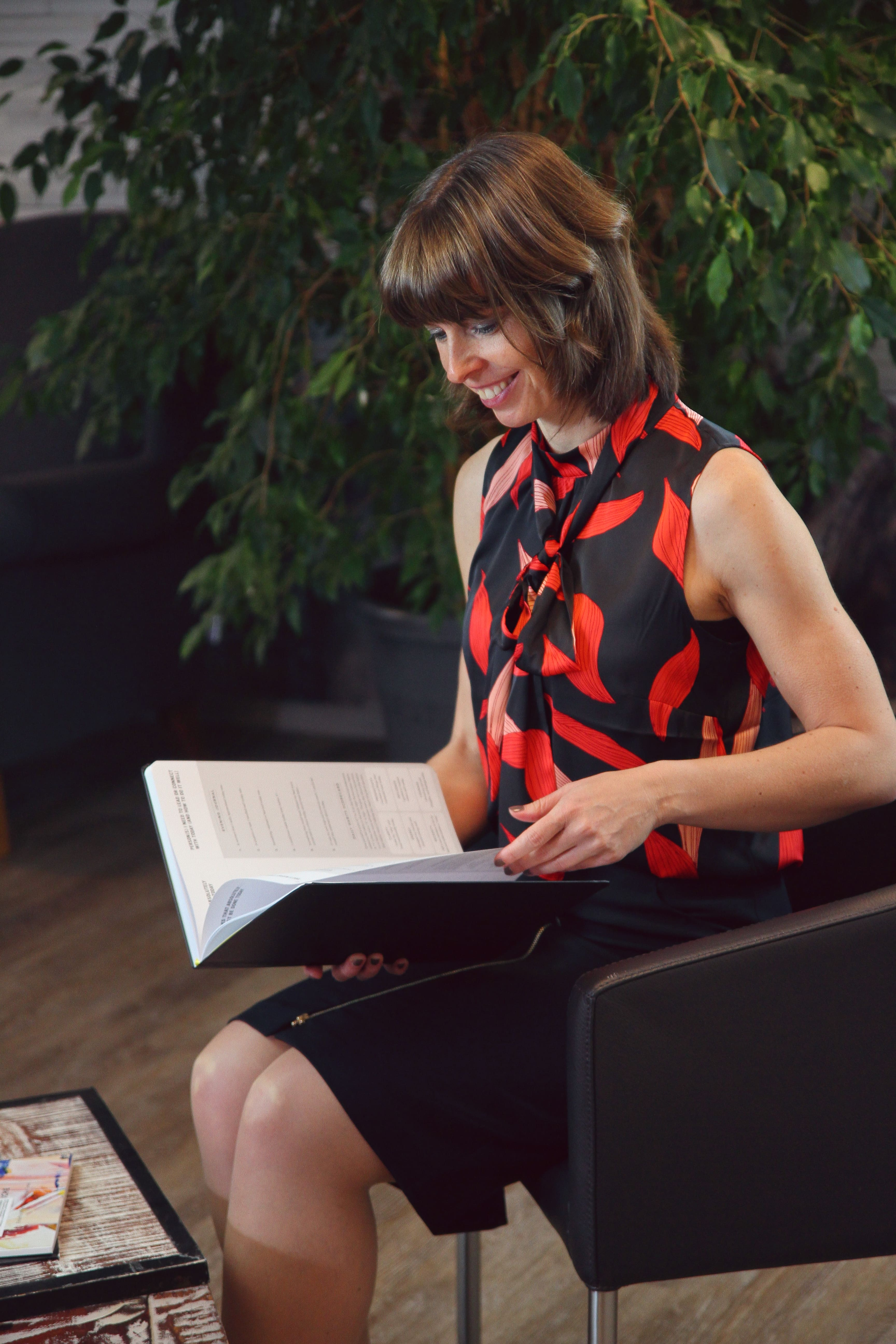 Janine Gruner sitzend und lesend im buisness Look
